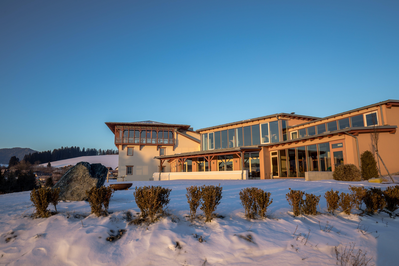Sie sehen eine Außenansicht vom JUFA Hotel Knappenberg in der Abenddämmerung im Winter. JUFA Hotels bietet erholsamen Familienurlaub und einen unvergesslichen Winter- und Wanderurlaub.