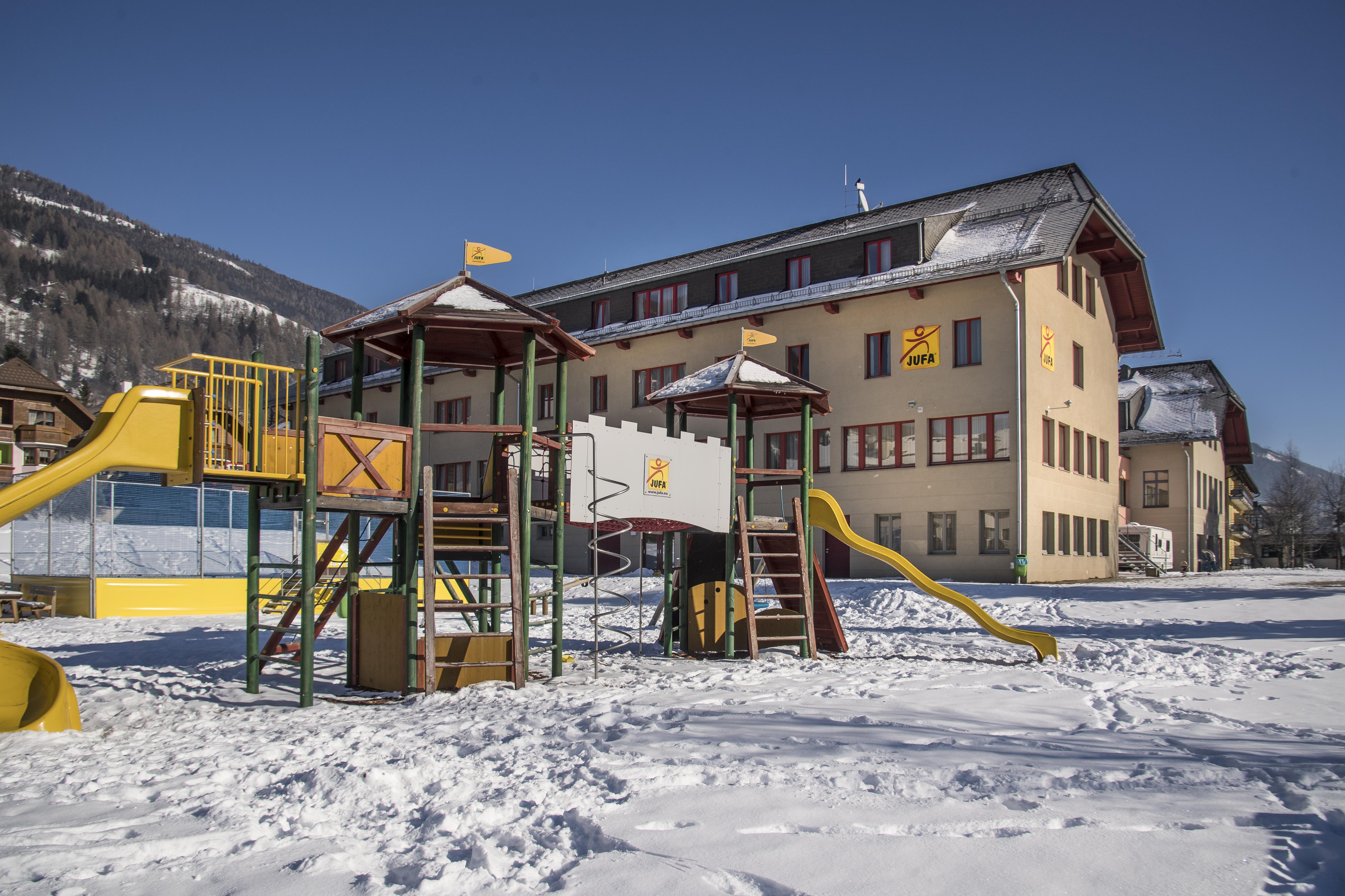 Hotelansicht vom JUFA Hotel Lungau mit Kletterburg vor blauem Himmel im Winter. JUFA Hotels bieten erholsamen Familienurlaub und einen unvergesslichen Winterurlaub.