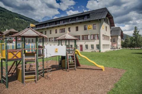 Außenansicht vom JUFA Hotel Lungau mit Kletterburg im Sommer. JUFA Hotels bieten erholsamen Familienurlaub und einen unvergesslichen Winter- und Wanderurlaub.