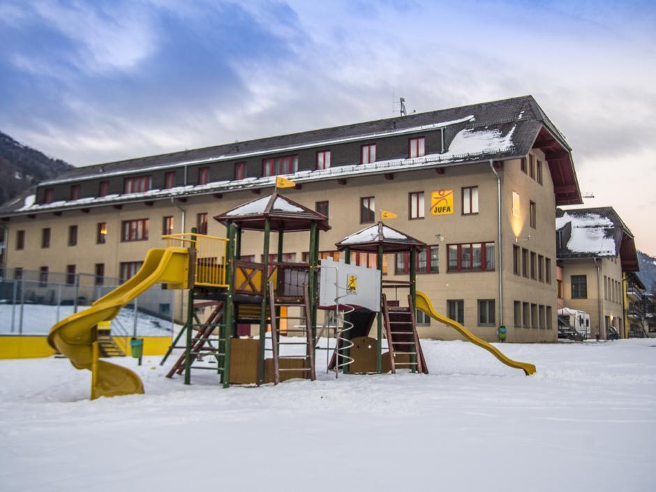 Außenansicht vom JUFA Hotel Lungau mit Kletterburg im Winter. JUFA Hotels bieten erholsamen Familienurlaub und einen unvergesslichen Winter- und Wanderurlaub.