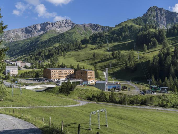Sie sehen eine Außenansicht vom JUFA Hotel Malbun – Alpin-Resort mit Bergen im Sommer. JUFA Hotels bietet erholsamen Familienurlaub und einen unvergesslichen Winter- und Wanderurlaub.