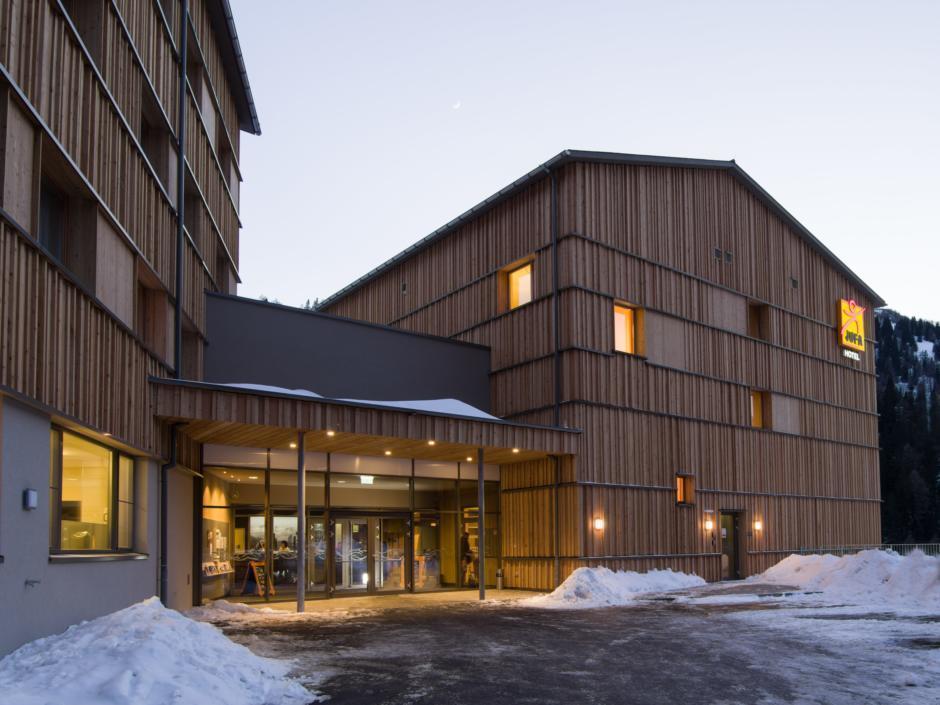 Aussenansicht mit Eingang bei winterlicher Abendstimmung vom JUFA Hotel Malbun Alpin-Resort. Der Ort für erholsamen Familienurlaub und einen unvergesslichen Winter- und Wanderurlaub.