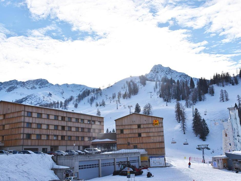 Sie sehen eine Hotelansicht vom JUFA Hotel Malbun – Alpin-Resort*** mit einer Garage im Winter. JUFA Hotels bietet erholsamen Familienurlaub und einen unvergesslichen Winterurlaub.