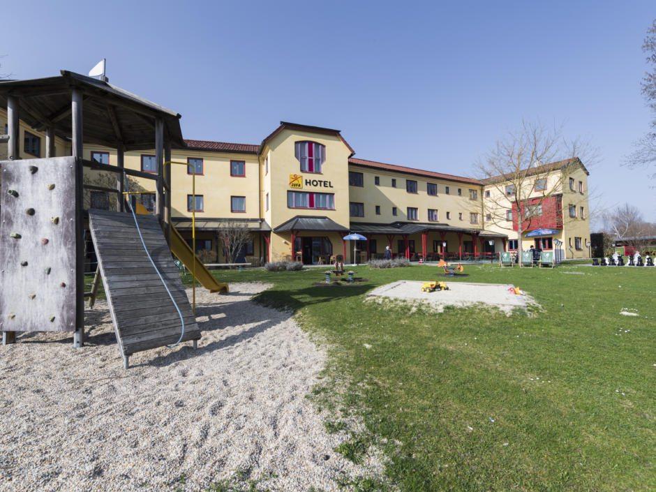Sie sehen eine Außenansicht vom JUFA Hotel Maria Lankowitz mit einem Spielplatz. JUFA Hotels bietet erholsamen Familienurlaub und einen unvergesslichen Winter- und Wanderurlaub.