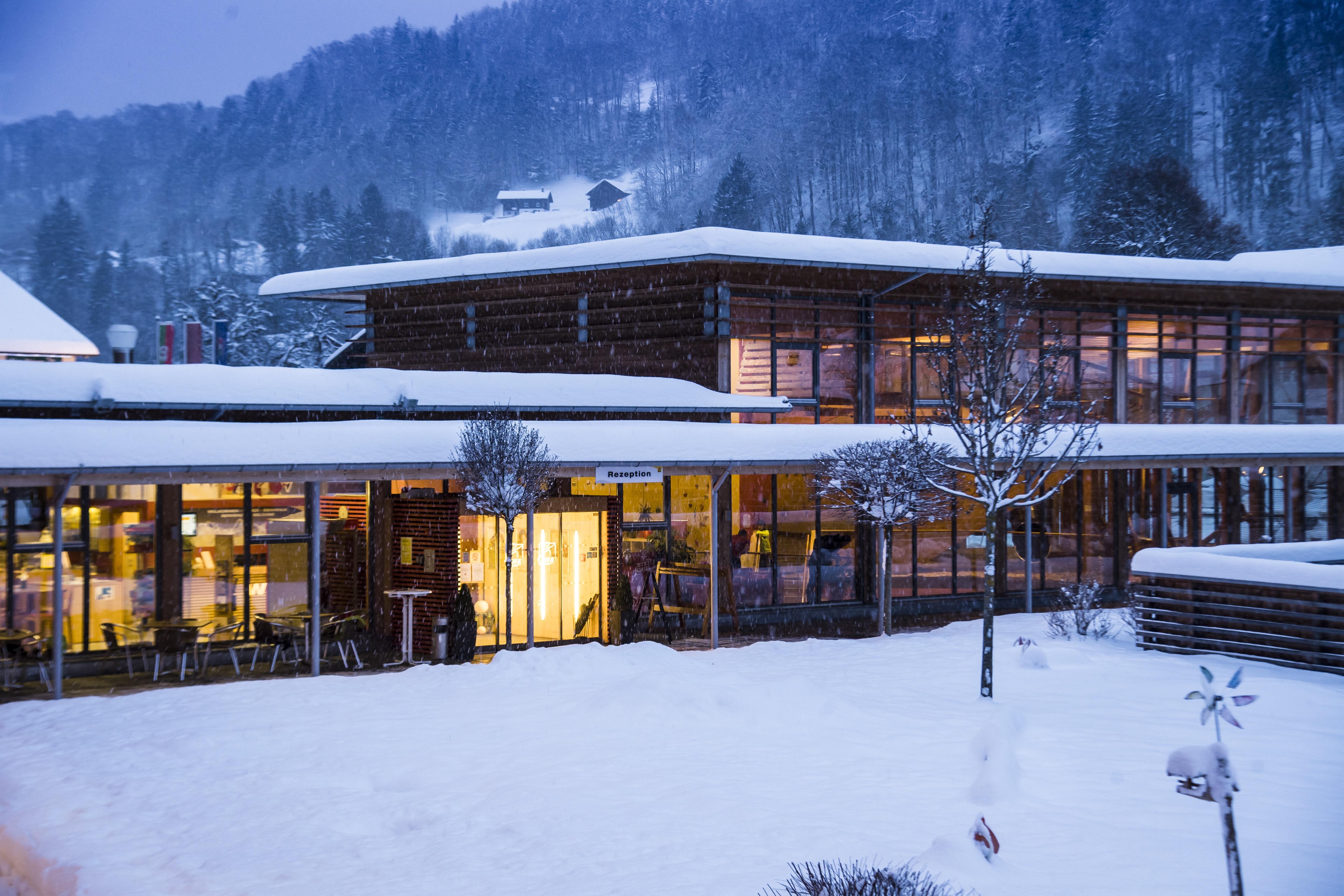 Aussenansicht mit Eingang im Winter vom JUFA Hotel Montafon in der Abenddämmerung. Der Ort für erholsamen Familienurlaub und einen unvergesslichen Winter- und Wanderurlaub.