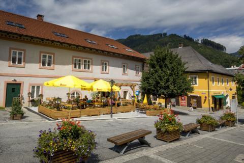 Sie sehen eine Außenansicht vom JUFA Hotel Murau mit Gastgarten im Sommer. JUFA Hotels bietet erholsamen Familienurlaub und einen unvergesslichen Winter- und Wanderurlaub.