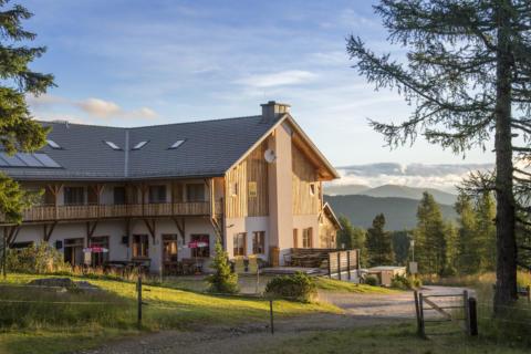 Außenansicht mit Anfang des Wanderwegs im Sommer vom JUFA Hotel Nockberge Almerlebnis. Der Ort für erholsamen Familienurlaub und einen unvergesslichen Winter- und Wanderurlaub.