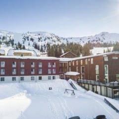 Sie sehen eine Außenansicht vom JUFA Hotel Planneralm – Alpin-Resort*** mit Bergblick im Winter. JUFA Hotels bietet erholsamen Familienurlaub und einen unvergesslichen Winterurlaub.