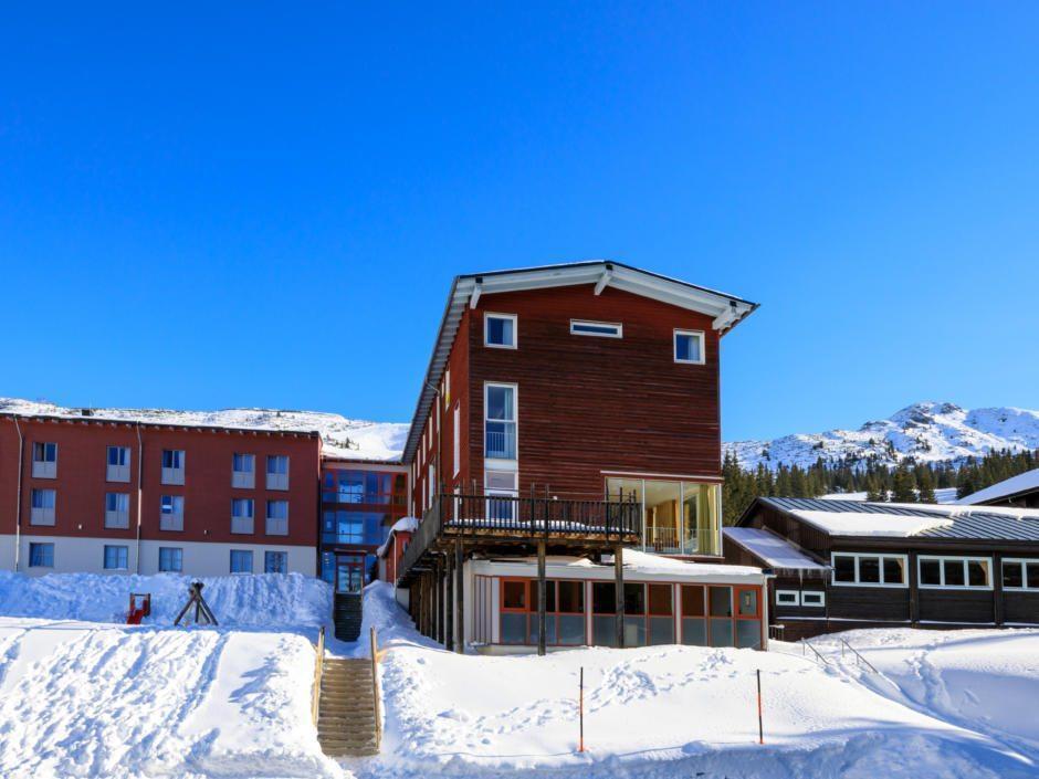 Sie sehen eine Hotelansicht vom JUFA Hotel Planneralm – Alpin-Resort im Winter. JUFA Hotels bietet erholsamen Familienurlaub und einen unvergesslichen Winterurlaub.