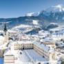 Sie sehen eine Außenansicht vom JUFA Hotel Pyhrn-Priel mit Bergen im Winter. JUFA Hotels bietet erholsamen Familienurlaub und einen unvergesslichen Winterurlaub.