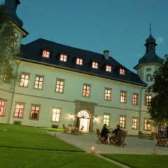 Aussenansicht mit Terrasse vom JUFA Hotel Schloss Röthelstein bei sommerlicher Abendstimmung. Der Ort für märchenhafte Hochzeiten und erfolgreiche und kreative Seminare.