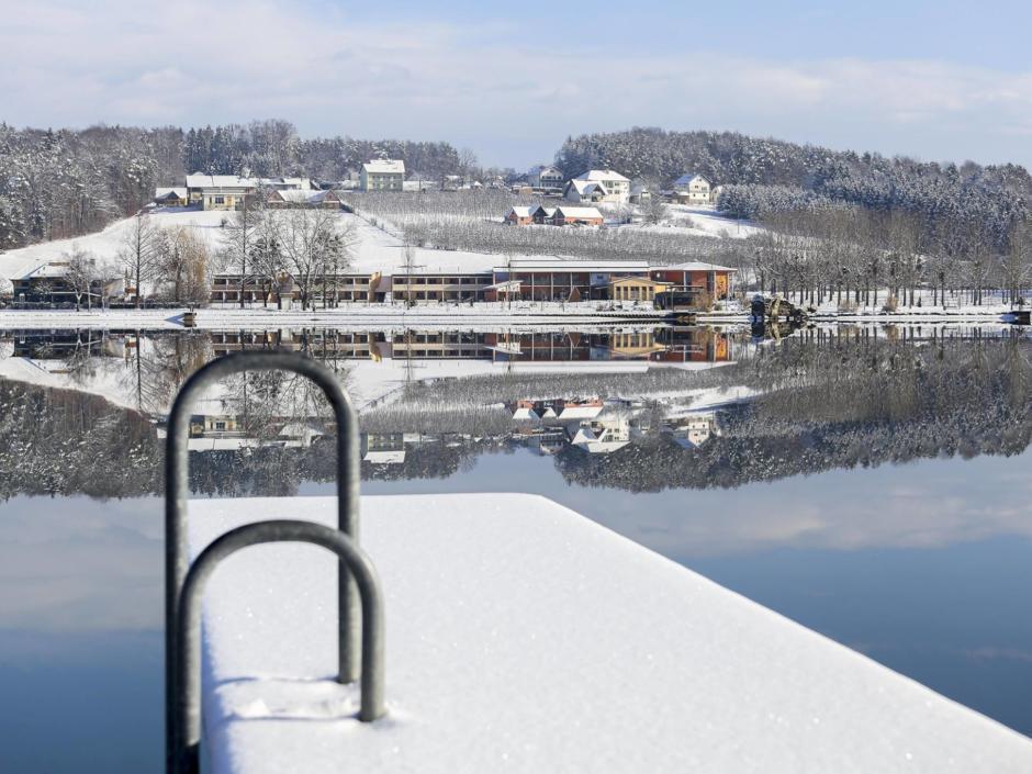 Sie sehen eine Außenansicht vom JUFA Hotel Stubenbergsee mit See und verschneitem Steg im Winter. JUFA Hotels bietet kinderfreundlichen und erlebnisreichen Urlaub für die ganze Familie.