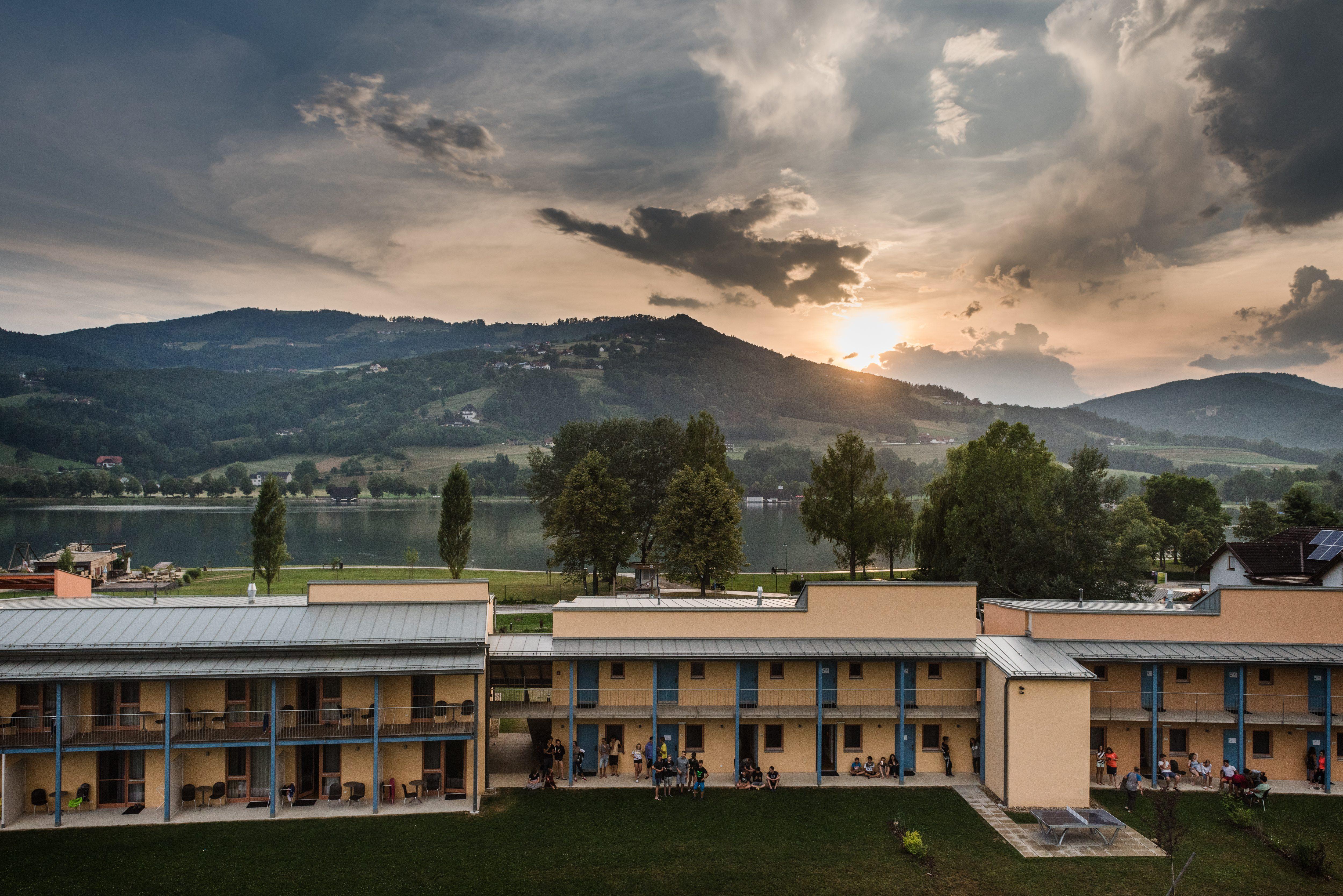Sie sehen eine Außenansicht vom JUFA Hotel Stubenbergsee mit Seeblick im Sommer. JUFA Hotels bietet kinderfreundlichen und erlebnisreichen Urlaub für die ganze Familie.