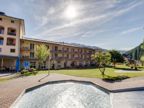 Sie sehen eine Außenansicht vom JUFA Hotel Veitsch mit Kinderbecken im Sommer. JUFA Hotels bietet kinderfreundlichen und erlebnisreichen Urlaub für die ganze Familie.