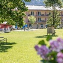 Sie sehen eine Außenansicht vom JUFA Hotel Veitsch mit Liegewiese und Kinderrutsche im Sommer. JUFA Hotels bietet kinderfreundlichen und erlebnisreichen Urlaub für die ganze Familie.