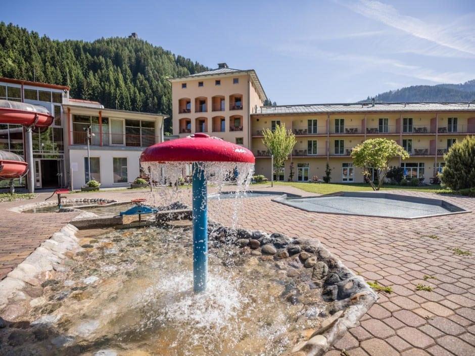 Sie sehen eine Außenansicht vom JUFA Hotel Veitsch mit Pilzbrunnen und Kinderbecken im Sommer. JUFA Hotels bietet kinderfreundlichen und erlebnisreichen Urlaub für die ganze Familie.