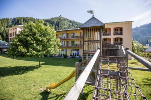 Sie sehen eine Außenansicht vom JUFA Hotel Veitsch mit Spielplatz im Sommer. JUFA Hotels bietet kinderfreundlichen und erlebnisreichen Urlaub für die ganze Familie.