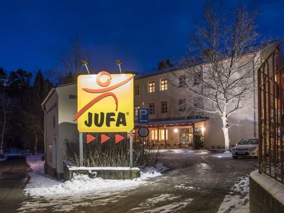 Sie sehen eine Außenansicht vom JUFA Hotel Waldviertel mit beleuchtetem Wegweiser am Abend und im Winter. JUFA Hotels bietet erholsamen Familienurlaub und einen unvergesslichen Winterurlaub.