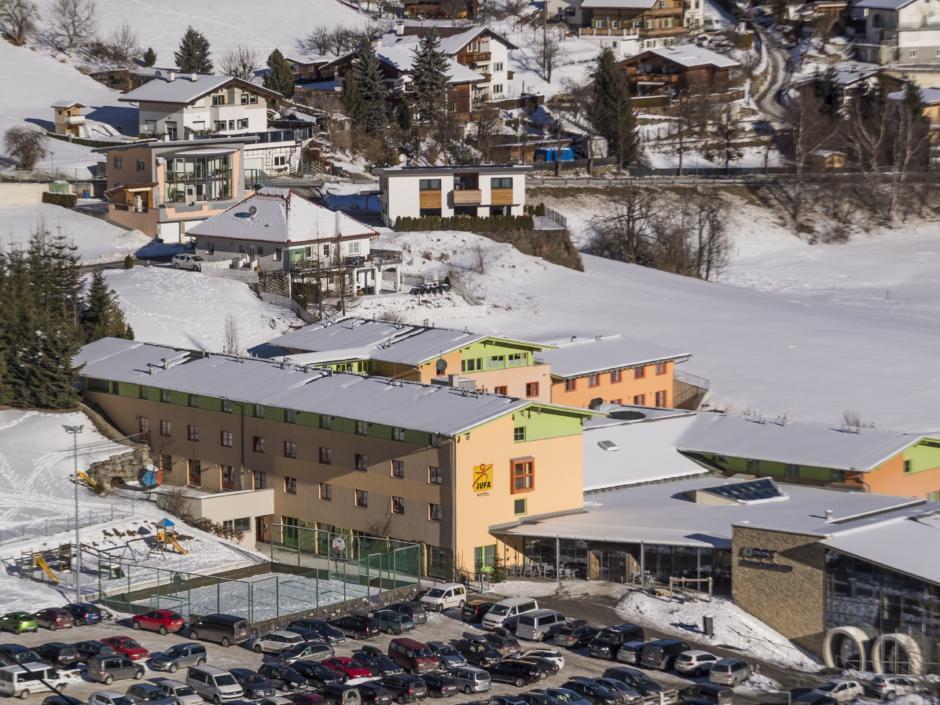 Sie sehen eine Außenansicht vom JUFA Hotel Wipptal mit Parkplatz aus der Vogelperspektive im Winter. JUFA Hotels bietet erholsamen Familienurlaub und einen unvergesslichen Winterurlaub.
