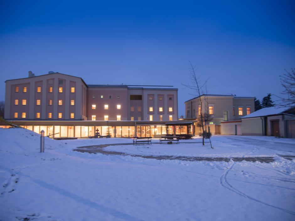Sie sehen eine Außenansicht vom JUFA Weinviertel - Hotel zur Eselsmühle bei Abendstimmung im Winter. JUFA Hotels bietet erholsamen Familienurlaub und einen unvergesslichen Winterurlaub.