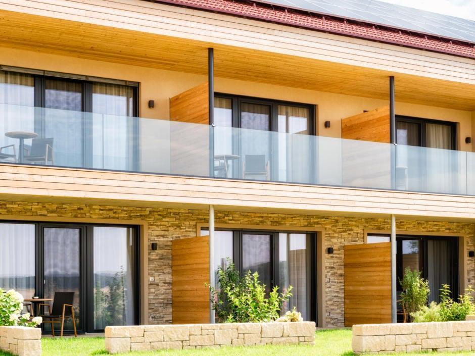 Sie sehen eine Außenansicht des Neubaus vom JUFA Hotel Neutal – Landerlebnis mit Balkonen und Terrassen im Sommer. JUFA Hotels bietet kinderfreundlichen und erlebnisreichen Urlaub für die ganze Familie.