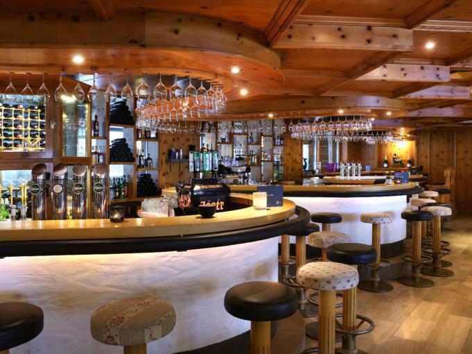 Sie sehen die Hotelbar im JUFA Alpenhotel Saalbach**** mit Barhockern. JUFA Hotels bietet erholsamen Familienurlaub und einen unvergesslichen Winterurlaub.