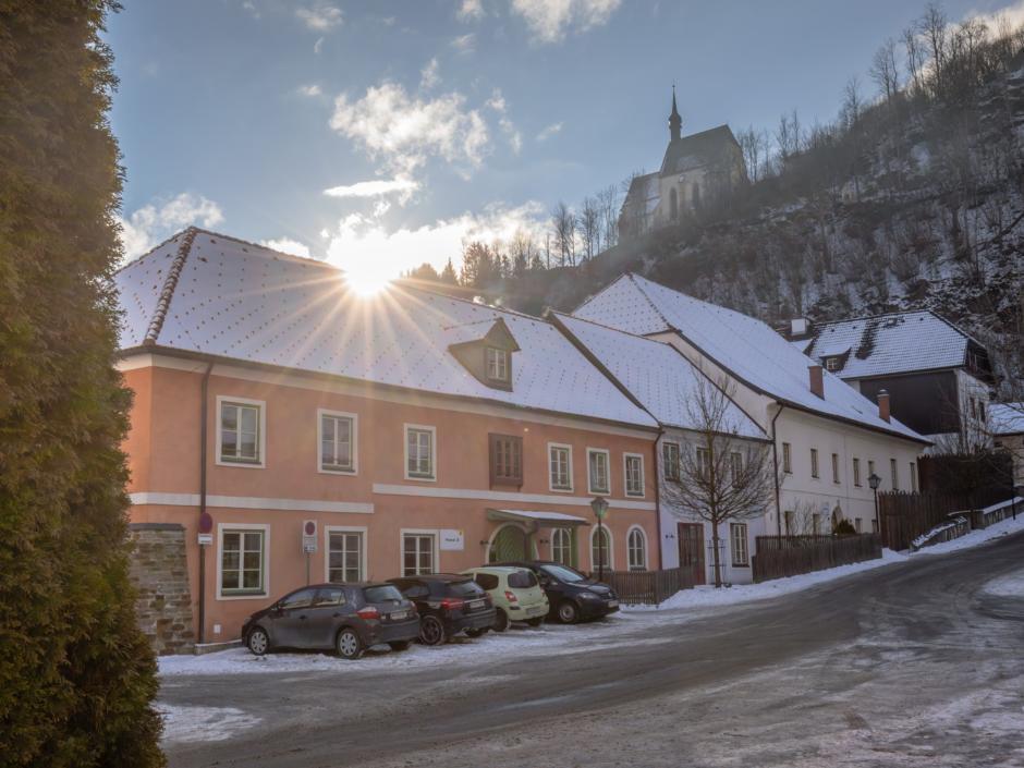 Sie sehen den Hoteleingang vom JUFA Hotel Murau mit Parkplatz im Winter. JUFA Hotels bietet erholsamen Familienurlaub und einen unvergesslichen Winterurlaub.