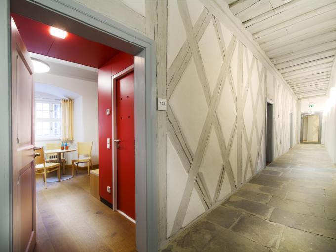 Sie sehen den Hotelgang im JUFA Hotel Kronach – Festung Rosenberg mit einem Zimmer. JUFA Hotels bietet kinderfreundlichen und erlebnisreichen Urlaub für die ganze Familie.