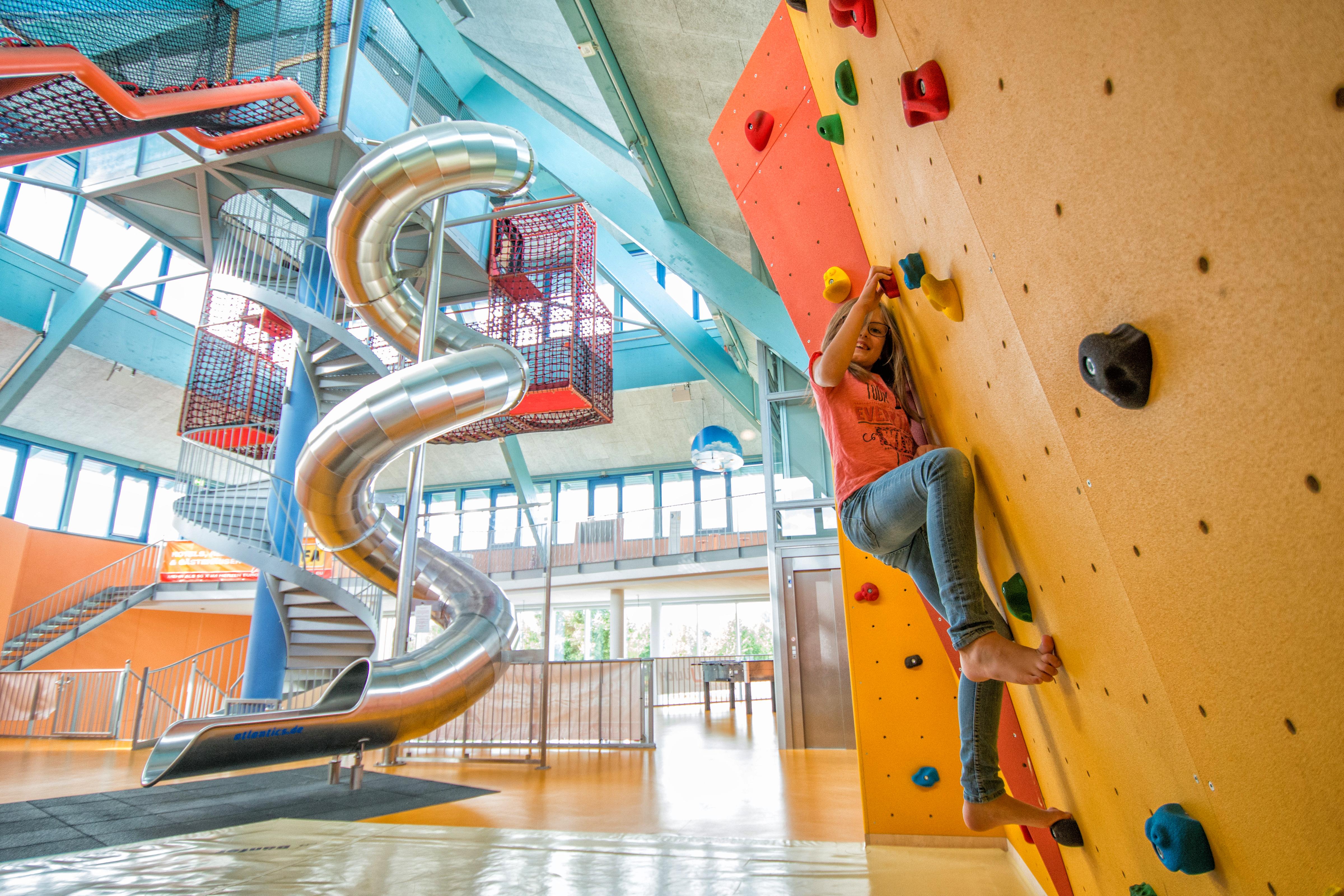 Ein Mädchen beim Klettern auf der Boulderwand im Indoorspielbereich im JUFA Hotel Jülich. JUFA Hotels bieten erholsamen Familienurlaub und einen unvergesslichen Winter- und Wanderurlaub.