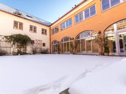Sie sehen den Innenhof vom JUFA Hotel Oberwölz mit großflächigen Fenstern im Winter. JUFA Hotels bietet erholsamen Familienurlaub und einen unvergesslichen Winterurlaub.