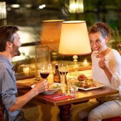Sie sehen ein Paar beim Abendessen  in der Pizzeria La Trattoria im JUFA Alpenhotel Saalbach****. Der Ort für erholsamen Familienurlaub und einen unvergesslichen Winter- und Wanderurlaub.