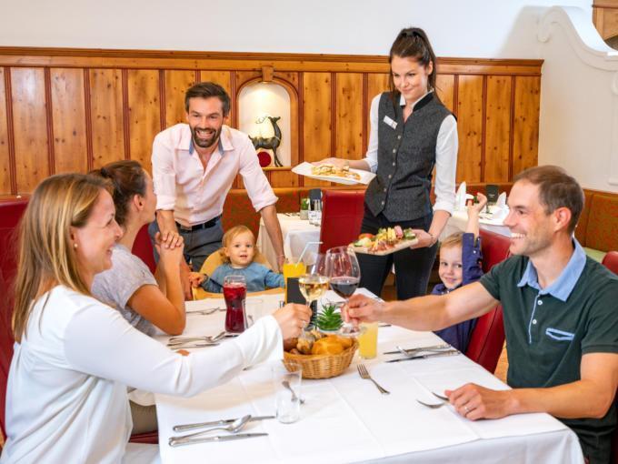 Sie sehen eine Familie beim Abendessen im JUFA Alpenhotel Saalbach****. Der Ort für erholsamen Familienurlaub und einen unvergesslichen Winter- und Wanderurlaub.