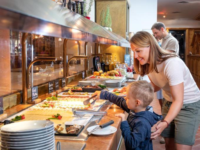 Sie sehen eine Familie beim Frühstück am Buffet des JUFA Alpenhotel Saalbach****. Der Ort für erholsamen Familienurlaub und einen unvergesslichen Winter- und Wanderurlaub.