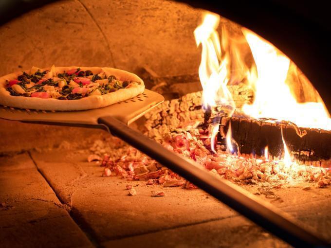 Sie sehen eine  Pizza, die im Holzofen  gebacken wird. JUFA Hotels bietet erholsamen Familienurlaub und einen unvergesslichen Winter- und Wanderurlaub.