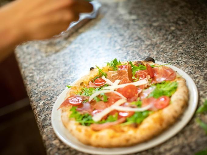 Sie sehen eine Pizza, die fertig belegt wird. JUFA Hotels bietet erholsamen Familienurlaub und einen unvergesslichen Winter- und Wanderurlaub.