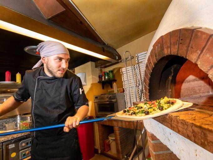 Sie sehen einen Pizzakoch, der eine Pizza in den Holzofen schiebt. JUFA Hotels bietet erholsamen Familienurlaub und einen unvergesslichen Winter- und Wanderurlaub.