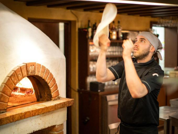 Sie sehen einen Pizzakoch, der einen Pizzateig wirft. JUFA Hotels bietet erholsamen Familienurlaub und einen unvergesslichen Winter- und Wanderurlaub.
