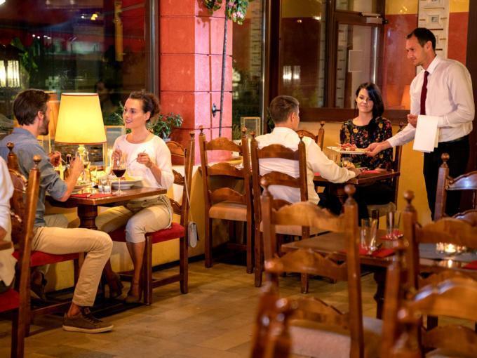 Sie sehen Gäste beim Abendessen in der Pizzeria La Trattoria im JUFA Alpenhotel Saalbach****. Der Ort für erholsamen Familienurlaub und einen unvergesslichen Winter- und Wanderurlaub.