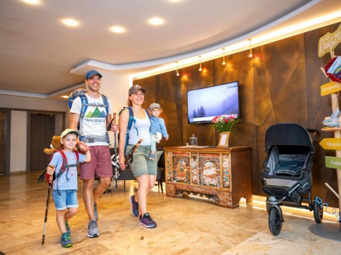 Sie sehen eine Familie in der Lobby des JUFA Alpenhotel Saalbach****, die zum Wandern aufbricht. JUFA Hotels bietet erholsamen Familienurlaub und einen unvergesslichen Winter- und Wanderurlaub.