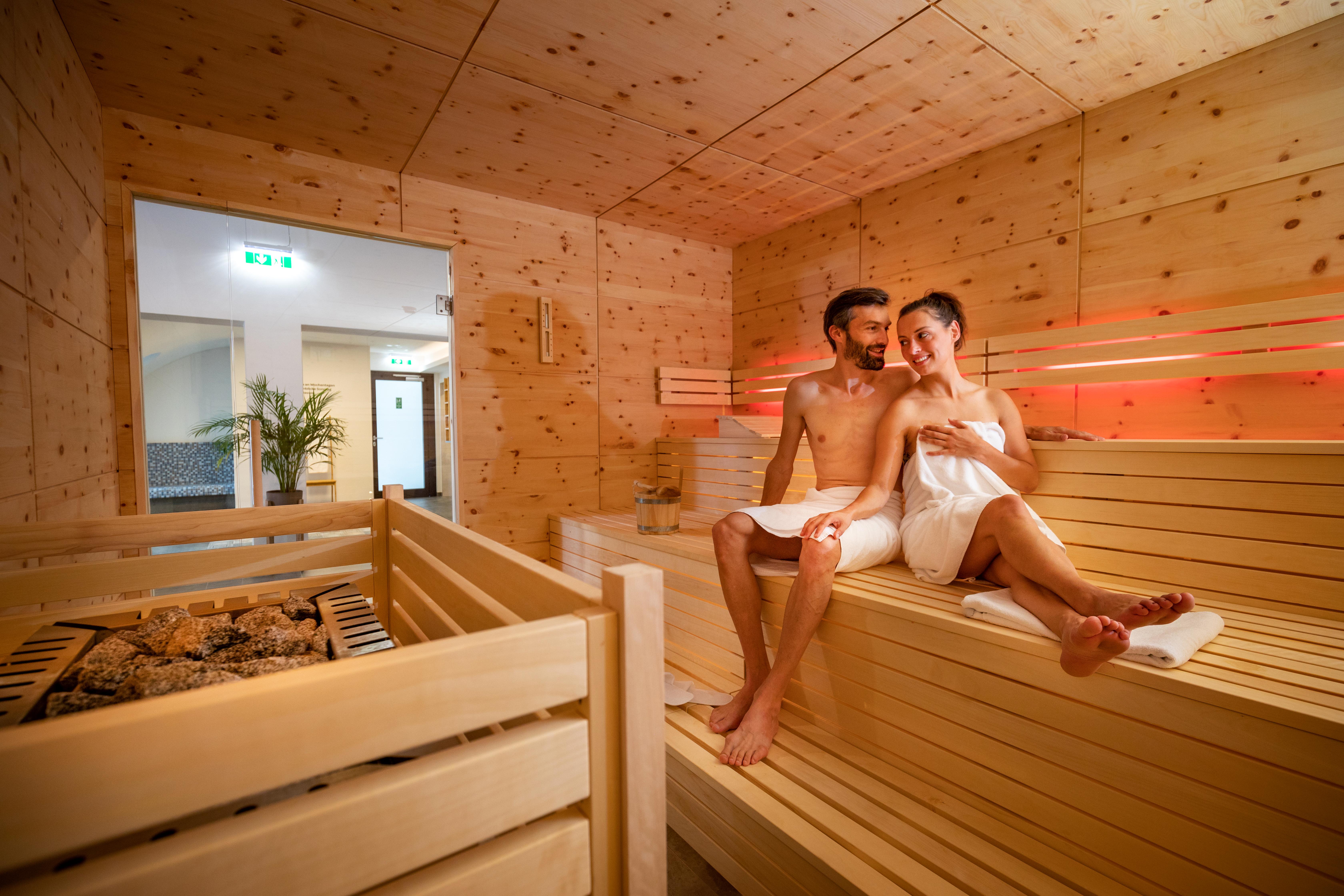 Sie sehen ein Paar, das sich im Saunabereich des JUFA Alpenhotel Saalbach**** entspannt. JUFA Hotels bietet erholsamen Familienurlaub und einen unvergesslichen Winter- und Wanderurlaub.