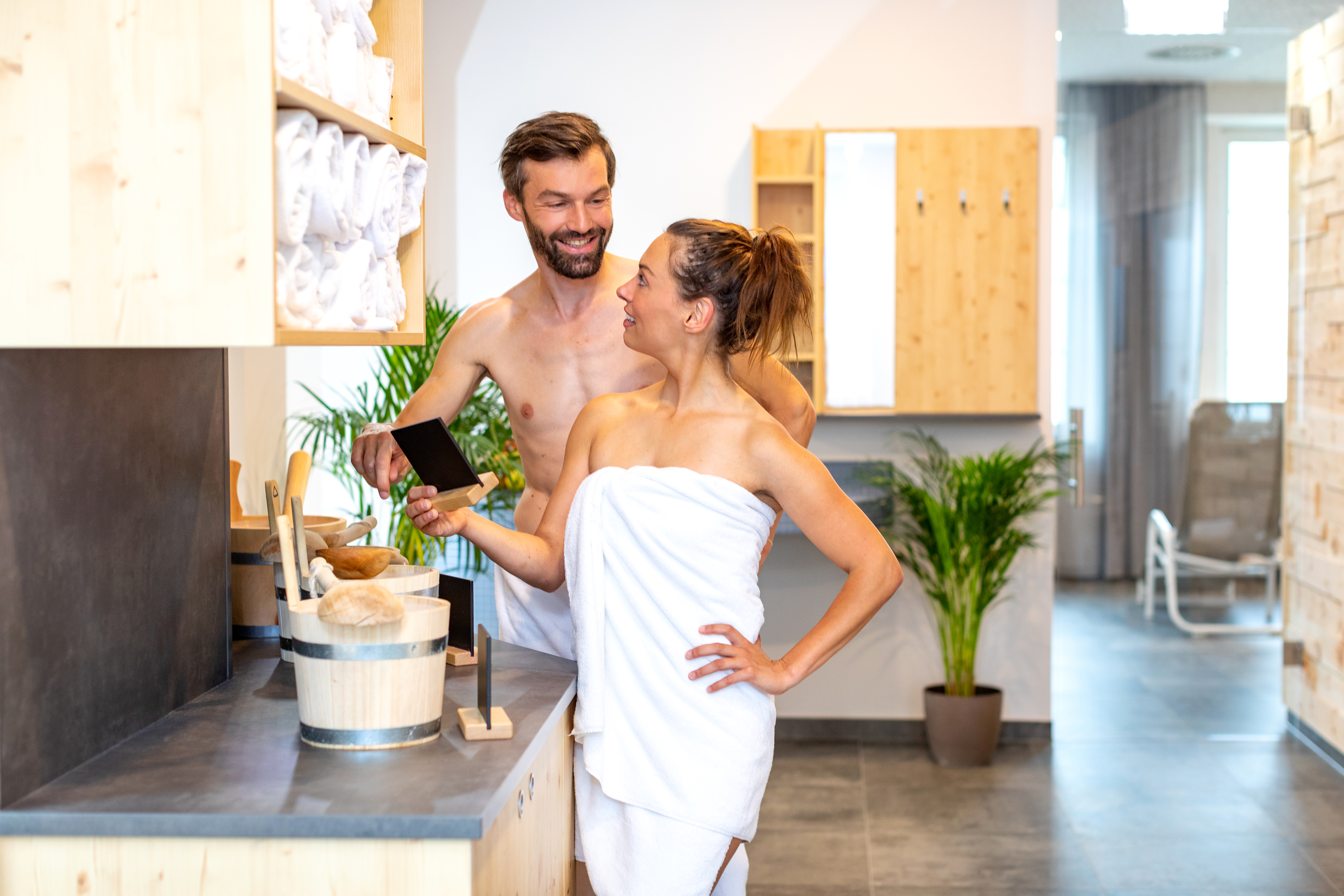 Sie sehen ein Paar, das sich im Wellnessbereich des JUFA Alpenhotel Saalbach**** entspannt. JUFA Hotels bietet erholsamen Familienurlaub und einen unvergesslichen Winter- und Wanderurlaub.