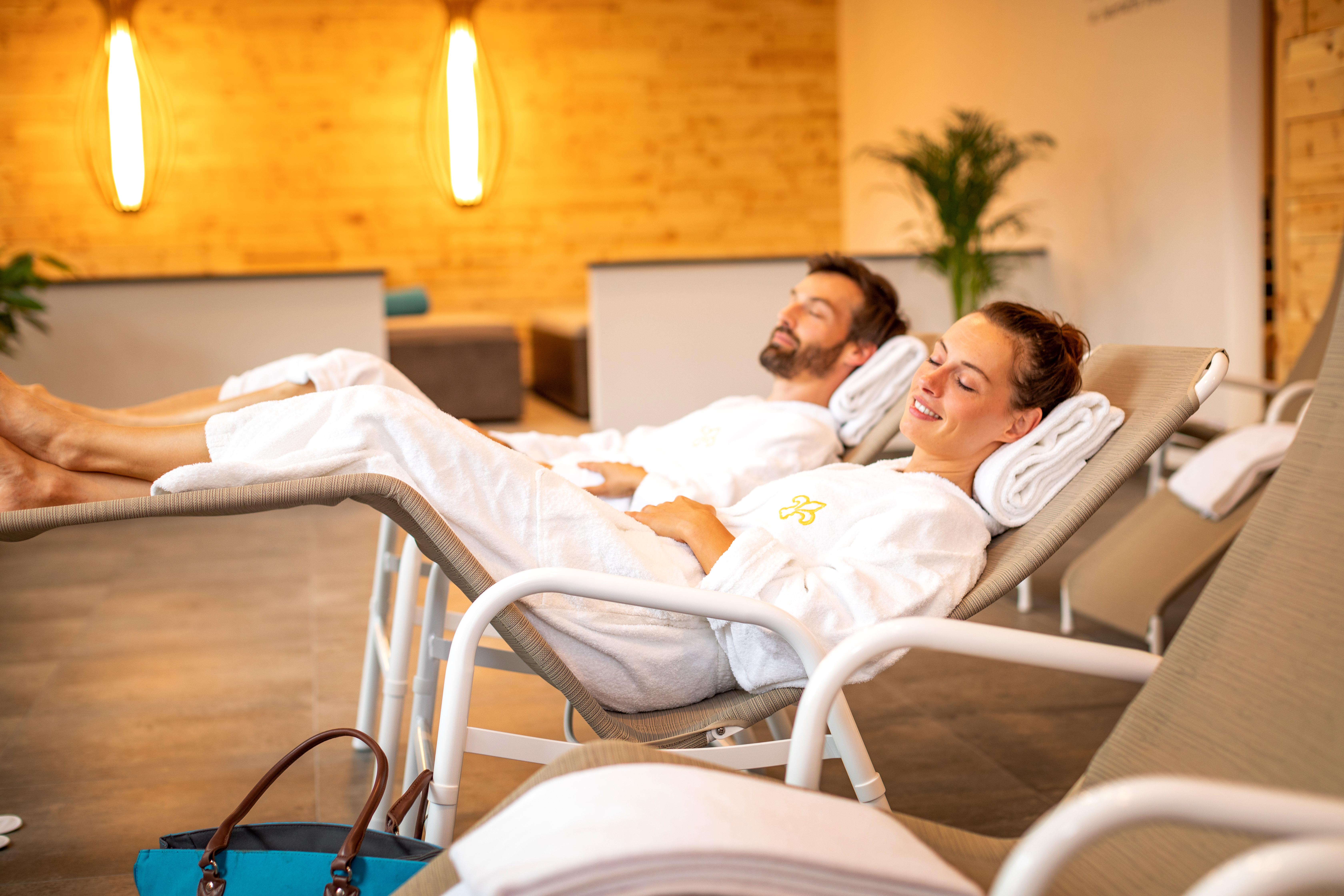 Sie sehen ein Paar, das sich im Ruhebereich der Wellnessanlage des JUFA Alpenhotel Saalbach**** entspannt. JUFA Hotels bietet erholsamen Familienurlaub und einen unvergesslichen Winter- und Wanderurlaub.