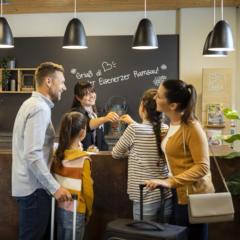 Sie sehen eine Familie bei ihrer Ankunft an der Rezeption.  Das JUFA Hotel Eisenerz ist der ideale Ausgangspunkt für Ihren Wander- und Winterurlaub
