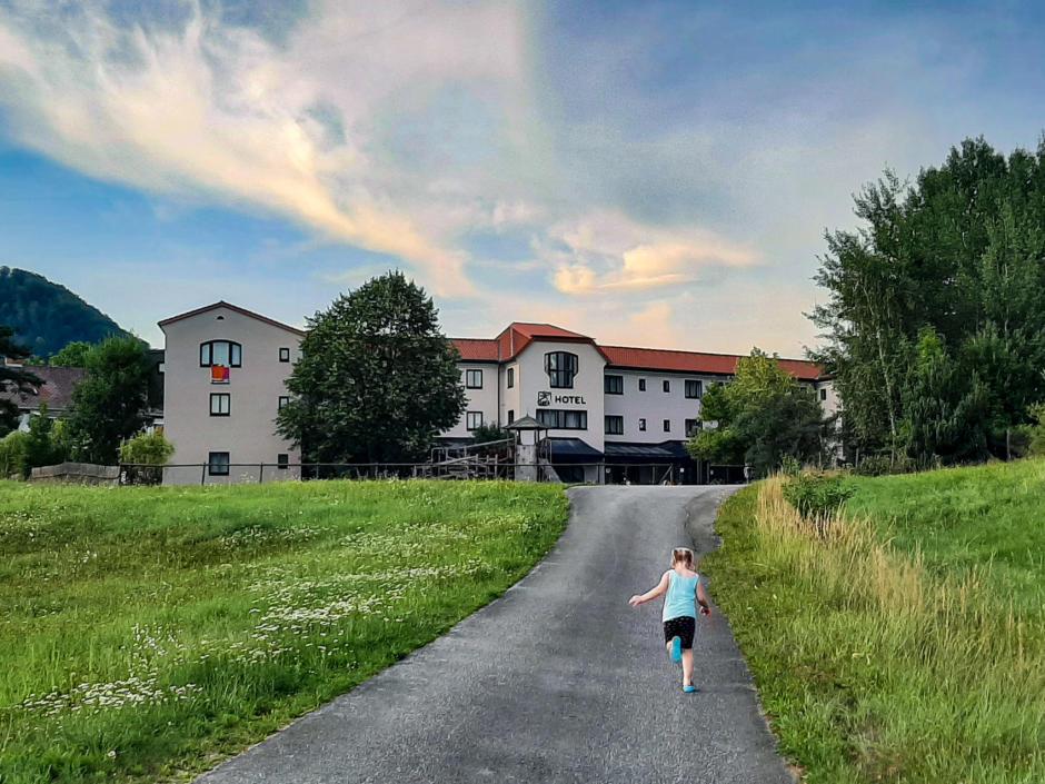 Sie sehen ein Kind, das den Weg zum Hotel entlang läuft. JUFA Hotels bietet erholsamen Familienurlaub und einen unvergesslichen Winter- und Wanderurlaub.