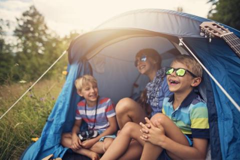 Sie sehen lachende Kinder unter einem Zelt in der Natur. JUFA Hotels bietet erholsamen Familienurlaub und einen unvergesslichen Winter- und Wanderurlaub.
