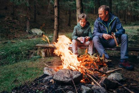 Sie sehen einen Vater mit seinem Sohn am Lagerfeuer im Wald sitzen. JUFA Hotels bietet erholsamen Familienurlaub und einen unvergesslichen Winter- und Wanderurlaub.