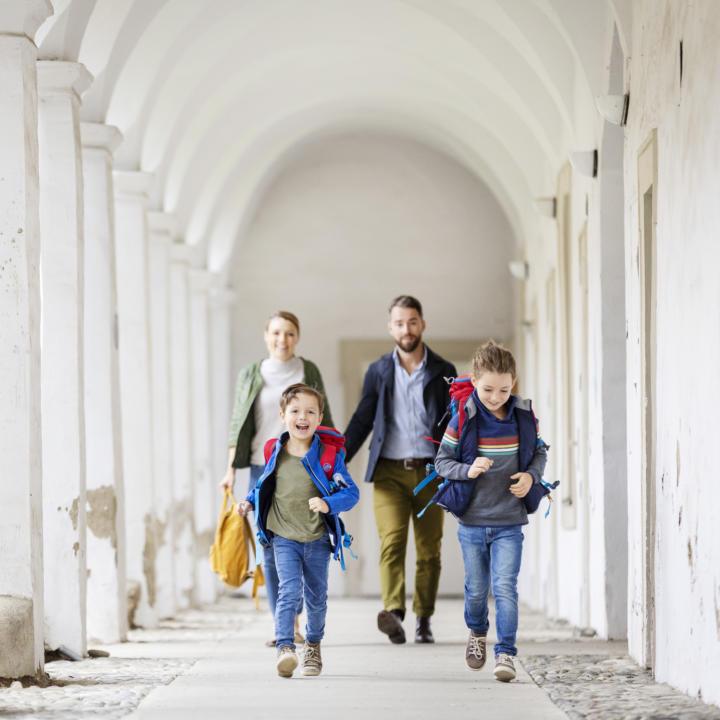 Sie sehen eine Familie von vorne mit Muter, Vater, Tochter, Sohn. Die Kinder laufen auf die Kamera zu, umgeben von den Klosterbögen vom JUFA Klosterhotel Judenburg. Der Ort für erholsamen Familienurlaub und einen unvergesslichen Winter- und Wanderurlaub.