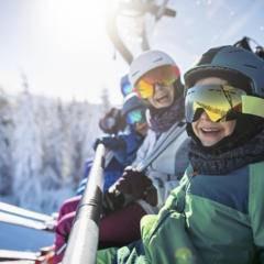 Sie sehen Jugendliche beim Skifahren in den Alpen auf dem Sessellift. JUFA Hotels bietet erholsamen Familienurlaub und einen unvergesslichen Winterurlaub.