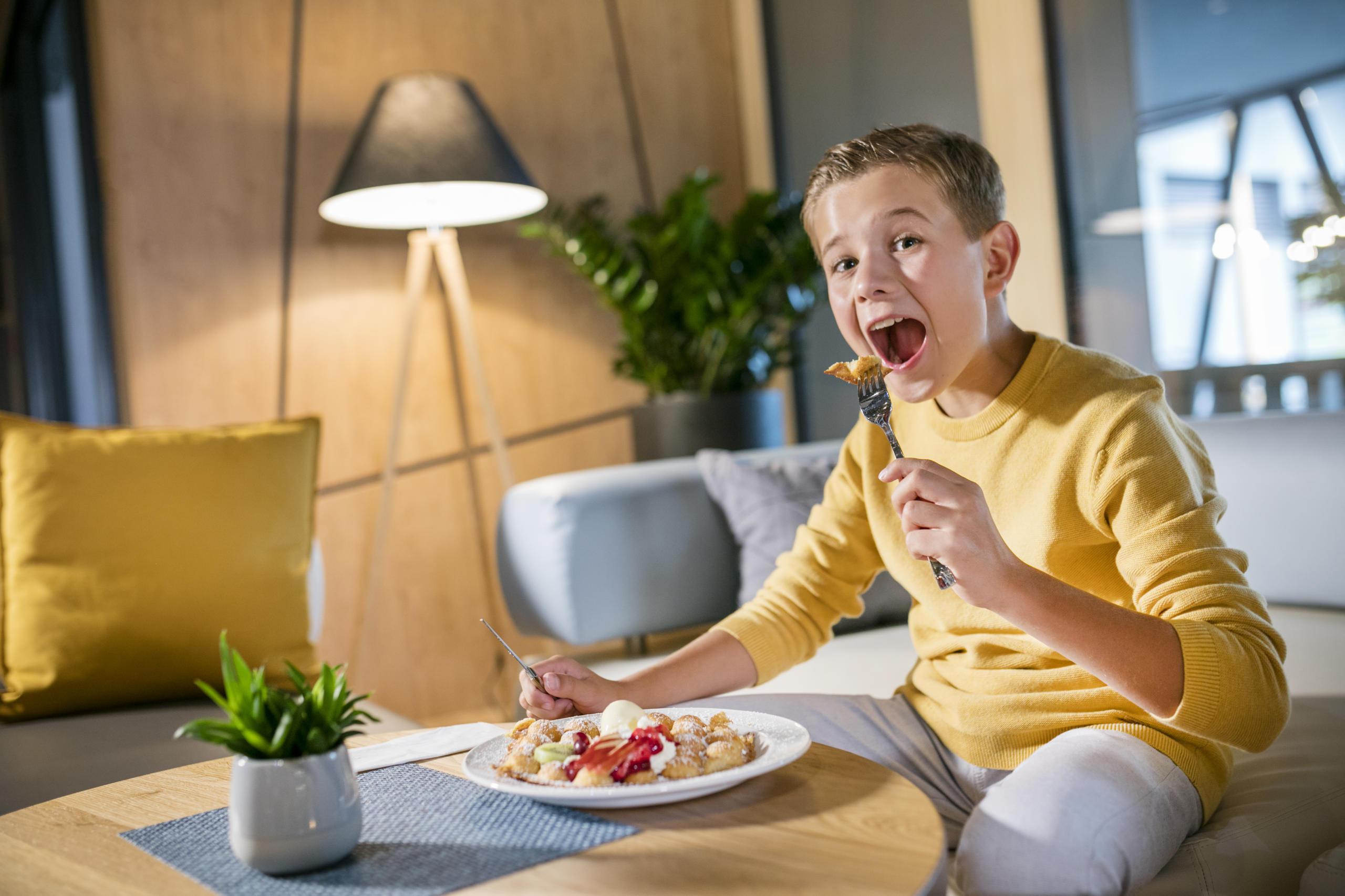 Sie sehen einen Junge eine Waffel mit Gabel essen im JUFA Hotel Weiz. Der Ort für kinderfreundlichen und erlebnisreichen Urlaub für die ganze Familie.