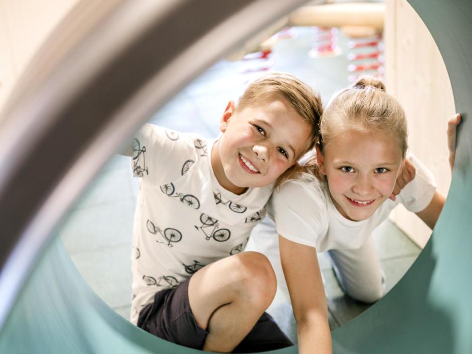 Sie sehen einen Jungen und ein Mädchen in einer Spielröhre im JUFA Hotel Weiz. Der Ort für kinderfreundlichen und erlebnisreichen Urlaub für die ganze Familie.